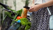 Girl standing with her bicycle and basket with shopping while texting on smartph Stock Footage