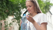 Girl taking water from her basket and drinking it, steadycam shot Stock Footage