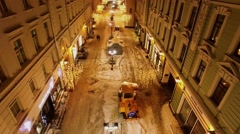 Machines removes snow from street at winter evening. Aerial view Stock Footage