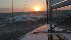 Sailboat in strong wind and big waves at sunset Stock Footage