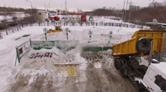 Truck unload snow to melting machine on station at winter day Stock Footage