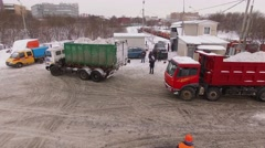 Workers and many trucks on snow melting at winter day. Stock Footage