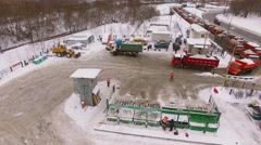 Lot of trucks with snow wait near melting station on road with traffic Stock Footage