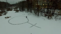 Females symbol on snow among trees not far from houses at winter Arkistovideo