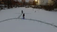 Man moves on skates with light by thin track on icy pond at winter Stock Footage