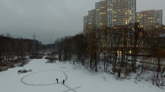 Man slides on skates with light by icy pond not far from house complex Stock Footage