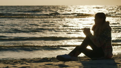 Young woman sitting on the beach on a cool windy day, drinking a hot drink from Stock Footage