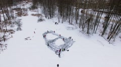 Snow-clad icy pond with people are skating among trees at winter Stock Footage