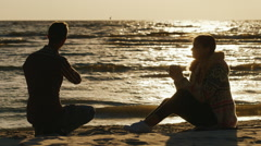 Romantic young couple relaxing on the beach or a lake on a cool day. Woman Stock Footage