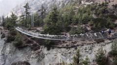 Tourists walk along suspension bridge Stock Footage