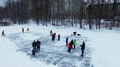 People get fun on icy pond not far from houses at winter evening. Arkistovideo