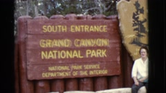1968: a woman posing in front of a large sign for the grand canyon national park Stock Footage