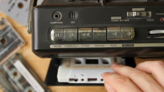 TMan's hand inserting the audio cassette into the retro tape player. Stock Footage