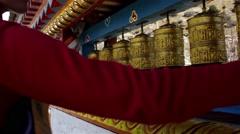 Traveler spinning golden prayer wheels Stock Footage