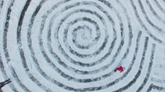 Kids and parents skate by icy pond with spirals and name Ann on snow Stock Footage