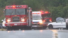 Firefighters and ambulance at car accident Stock Footage