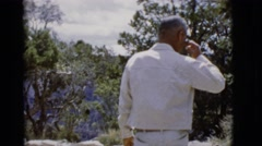 1968: man walks towards trees and view of mountains slowly before admiring view Stock Footage