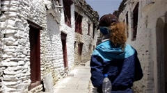 Female tourist in old white town Stock Footage