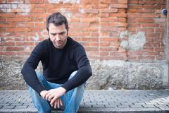 Sad man alone in the city streets Stock Photos