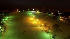 Illuminated snow slope with people and cityscape at winter Stock Footage
