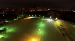 Illuminated snow slope with people among houses at winter Arkistovideo