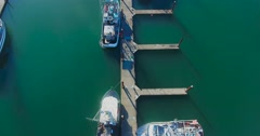 Aerial shot pans up to reveal boats at a coastal dock Stock Footage