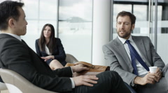 4K Business people chatting together in lobby of modern office building Stock Footage