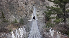 Mountain travel. Walking along suspension bridge on a windy day Stock Footage