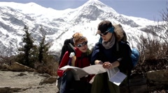 Tourists look at trekking map and discuss the route Stock Footage