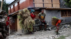 Typical scene of life in Nepal. Mother and a son carry load Stock Footage