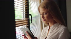 Close-up of charming blonde woman holding touch pad while standing near window Stock Footage