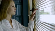 Close-up of cute blonde woman looking through out the blinds Stock Footage