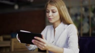 Young attractive blonde businesswoman in white shirt at coffee time working on Stock Footage