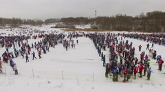 Crowd of people walk near start place with skiers before race Stock Footage