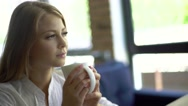Young thoughtful beautiful woman holding coffee cup and looking away while Stock Footage