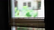 Blond office worker in white shirt peering through window blinds Stock Footage