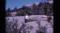 1968: woman wearing eyeglasses coming down a hill with bushes COTTONWOOD, Stock Footage