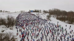 Large crowd of people skiing by hill during race Lyzhnia Rosii Stock Footage