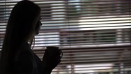 Silhouette young attractive girl holding a cup of coffee in the morning Stock Footage