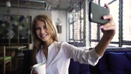Beautiful blond woman in white shirt taking selfie holding cup in the coffee bar Stock Footage