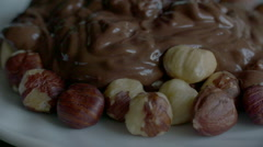Real Liquid Chocolate Covers Hazelnuts in slow motion scene Stock Footage