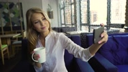 An attractive young blonde woman taking a self portrait on her cell phone at Stock Footage