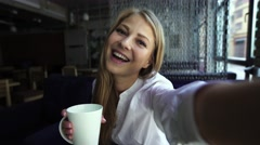 Pretty blonde woman taking self portrait while drinking coffee in a bar - Stock Footage