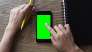 Female hand using smart mobile phone with a green screen on wooden table Stock Footage