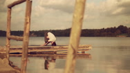 Man doing yoga asanas on a wooden quay on a background of a beautiful lake Stock Footage
