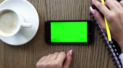 Hand holding smart phone with coffee on wood desk. Green screen and can be add Stock Footage