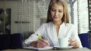 Young beautiful pensive woman drinking coffee and writing diary, book or notes Stock Footage