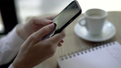 Side view, woman using a touch screen of smartphone on the wooden table, in cafe Stock Footage