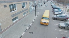 Yellow limousine drives by road with parking place near house. Aerial view Stock Footage