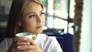 Beautiful blonde girl with nude make up wearing white blouse, sitting in cafe Stock Footage